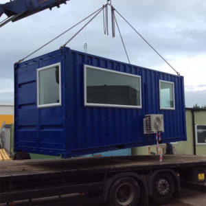 A converted shipping container in to an office loading on to a lorry