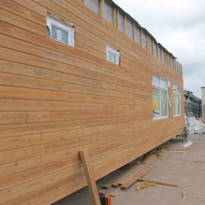 A building being covered in timber cladding