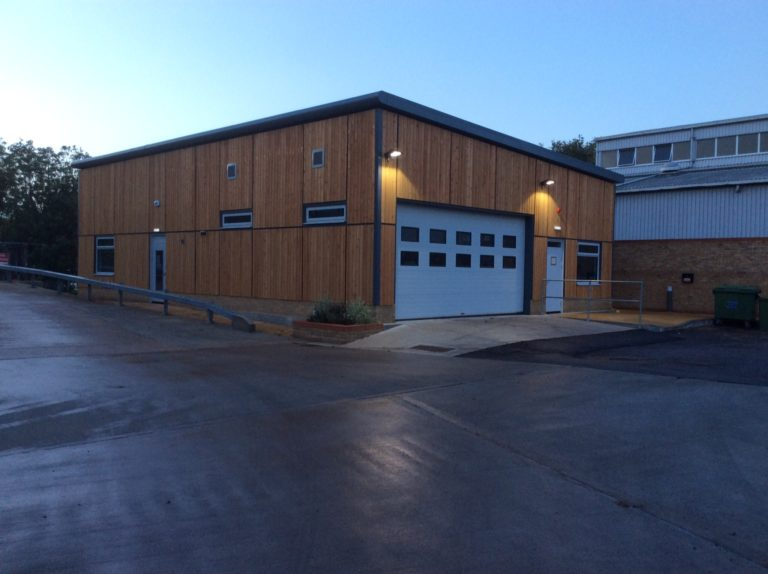Exterior of a modular office and workshop with large doorway.